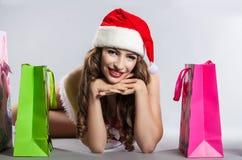 Flicka med jul som shoppar i hatten av Santa Claus Arkivfoto