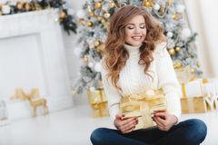 Flicka med julgåvan nära den härliga klädda julgranen Arkivbild