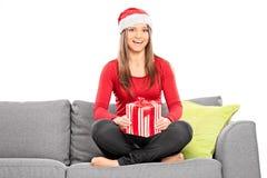 Flicka med julhatten som rymmer en gåva Royaltyfri Foto