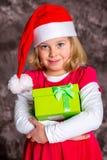 Flicka med jultomten lock och gåva Royaltyfria Foton
