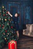 Flicka med jultreen Arkivfoto