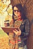 Flicka med kaffe och den digitala minnestavlan royaltyfri foto