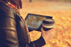 Flicka med kaffe och den digitala minnestavlan Arkivbilder