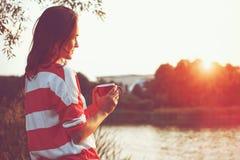 Flicka med kaffe på flodsoluppgång Arkivbild