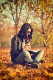 Flicka med kaffekoppen som läser en bok Arkivfoton