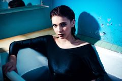 Flicka med kala skuldror som ligger i badrummet med kulört purpurfärgat vatten för begreppsframsida för skönhet blå ljus kvinna f royaltyfri bild