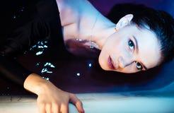Flicka med kala skuldror som ligger i badrummet med kulört purpurfärgat vatten för begreppsframsida för skönhet blå ljus kvinna f royaltyfria bilder