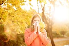 Flicka med kall rhinitis på höstbakgrund Nedgånginfluensasäsong I Arkivfoto