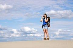 Flicka med kameran som fotvandrar i öken Arkivfoton