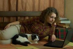 Flicka med katten och bärbara datorn Fotografering för Bildbyråer