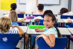 Flicka med klasskompisar i klassrum royaltyfri foto