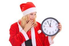 Flicka med klockan för santa hattholding Royaltyfri Foto