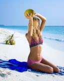 Flicka med kokosnöten på den vita sandstranden Arkivbild