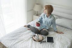 Flicka med koppen i hennes hand, kokkärl och minnestavla på en vit säng som ser i fönster Royaltyfria Foton