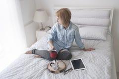Flicka med koppen i hennes hand, kokkärl och minnestavla på en vit säng som ser i fönster Royaltyfri Bild