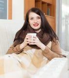 Flicka med koppen nära värmeelementet Royaltyfria Bilder