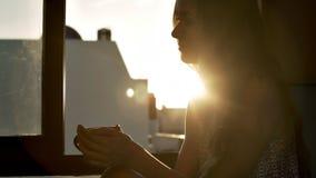 Flicka med koppkonturn vid fönstret på den ljusa solen stock video
