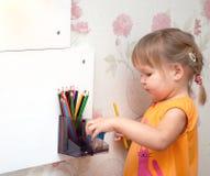 Flicka med kulöra blyertspennor Arkivfoto