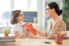 Flicka med läraren i klassrum arkivbild