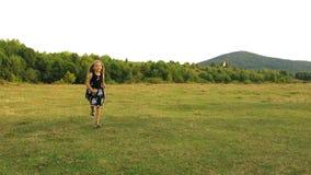 Flicka med lång spring för lockigt hår från avlägset Stöta ihop med gräsmattan in mot kameran arkivfilmer
