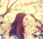 Flicka med långt blåsa hår i vårträdgård Royaltyfria Foton
