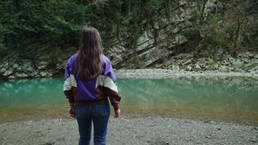 Flicka med långt blondish hår i ett omslag och jeans som kommer till en klar blå bergsjö, sikt från baksidan arkivfilmer