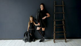 Flicka med långt hår i svart läderomslag lager videofilmer