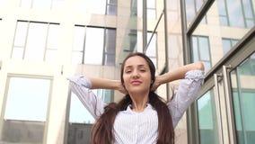 Flicka med långt hår nära en kontorsbyggnad stock video