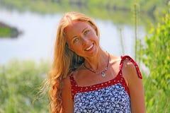 Flicka med långt hår som ler i natur Arkivfoto