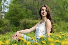 Flicka med långt hårsammanträde på gräsmattan fotografering för bildbyråer