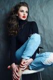 Flicka med långt lockigt hår i en svart halvpolokrage Arkivbilder
