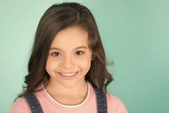 Flicka med leende på förtjusande framsida på blå bakgrund royaltyfria bilder