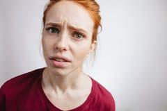 Flicka med ljust rödbrun hår och fräknar som in camera ser med ilsket uttryck royaltyfri fotografi