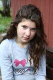 Flicka med lång lockig brun hårcloseupportriat Royaltyfria Bilder