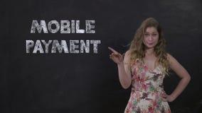 Flicka med lockigt hår som står på svart bakgrund med MOBIL BETALNING för titel arkivfilmer