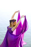 Flicka med lockigt hårflyg i den purpura klänningen Royaltyfria Bilder