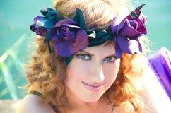 Flicka med lockigt hårflyg i den purpura klänningen Royaltyfri Fotografi