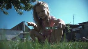 Flicka med loupen på gräsmatta stock video