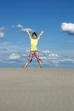 Flicka med lyftta händer på stranden royaltyfria foton