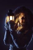 Flicka med lyktan som söker i natt Arkivfoto