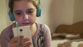 Flicka med lyssnande musik för hörlurar från smartphonen arkivfilmer