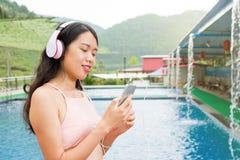 Flicka med lyssnande musik för telefon av simbassängen royaltyfria foton