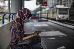 Flicka med maskeringen och smartphonen Arkivfoton
