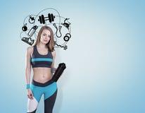 Flicka med matt yoga och sportsymboler, blått royaltyfria bilder