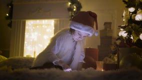 Flicka med minnestavlan nära julgranen lager videofilmer