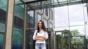 Flicka med minnestavlan på bakgrund av kontorsbyggnad lager videofilmer