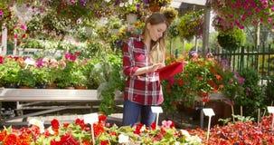 Flicka med minnestavlan som arbetar i blommande trädgård stock video