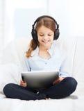 Flicka med minnestavlaPC och hörlurar hemma Arkivbilder
