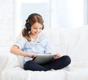 Flicka med minnestavlaPC och hörlurar hemma fotografering för bildbyråer