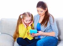 Flicka med modern som sitter på soffan genom att använda minnestavlan royaltyfri fotografi